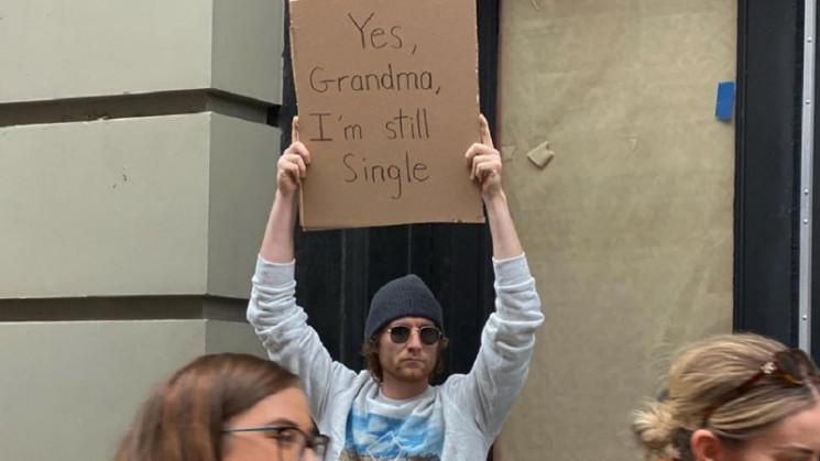 Дотепний хлопець вийшов на вулицю з плак…